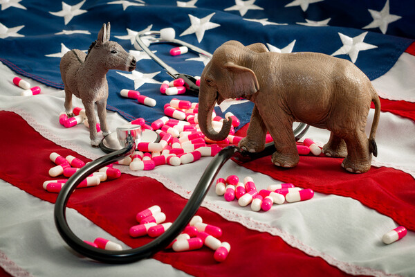 donkey and elephant figurines on an american flag standing among pills and a stethoscope