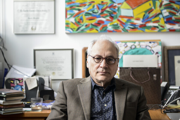 Charles Bernstein at his desk in his office with a colorful painting by his wife on the wall behind him