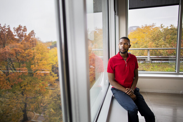 JD Goins sits near a window, looking out onto the beautiful fall colors on the Penn campus' trees.