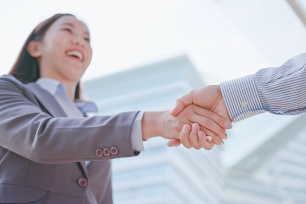 closeup of a young woman in a suit shaking hands with another person off-camera