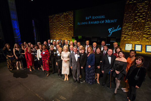 Alums and President Gutman pose for a photo on stage at the Gala