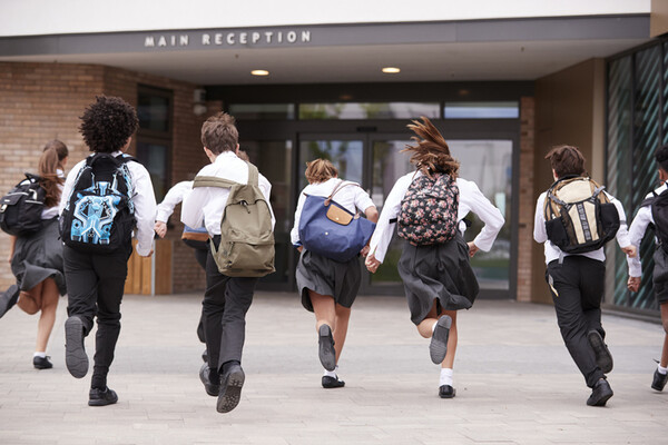 six kids in private school uniforms and backpacks running into school