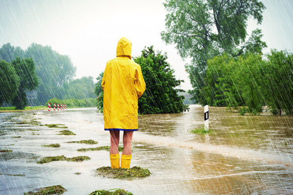 figure in rainstorm with back turned wearing a yellow raincoat and boots surrounded by flooding