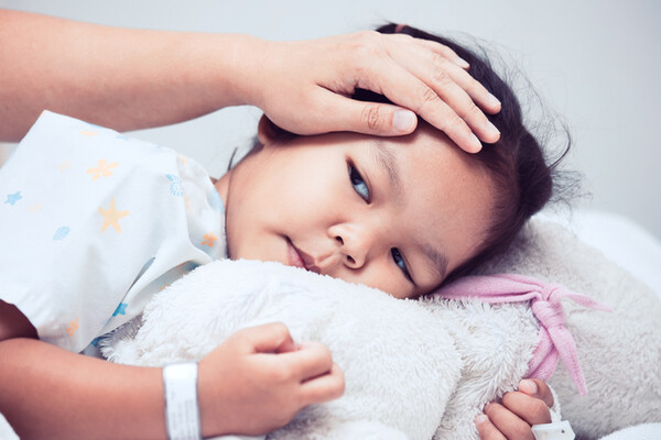 sick child in bed with adult hand on forehead