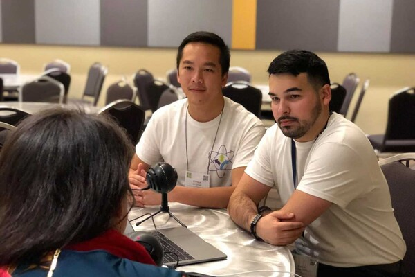 With a microphone between them, Enrique Lin-Shiao and Kevin Alicea-Torres sit for an interview with one of the subjects of their podcast.