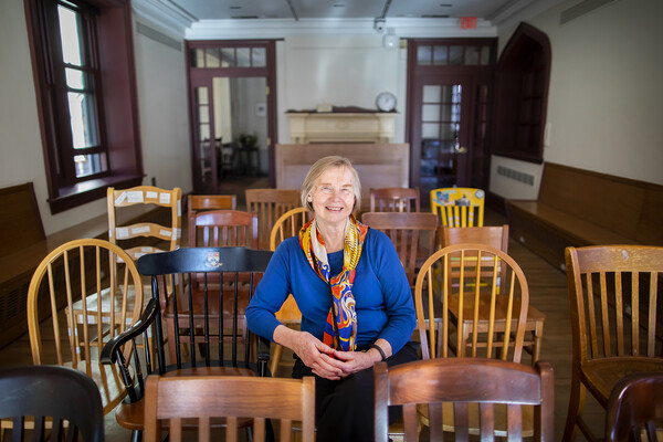 Deborah Burnham sits in Kelly Writers House, surrounded by wooden chairs