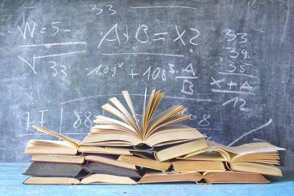 a stack of books in front of a chalkboard with math equations