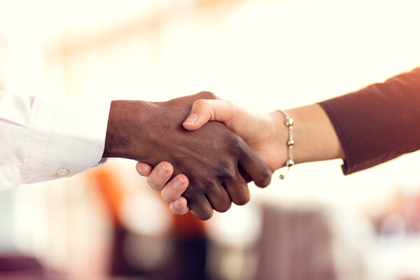 A black man and a white woman shaking hands