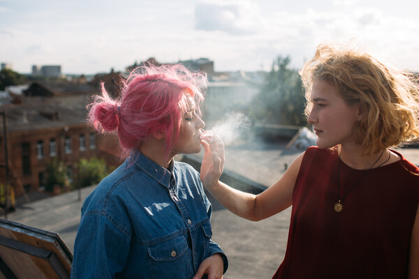 two teens smoking on a rooftop