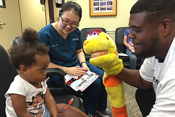 child at dentist office being mildly entertained yet skeptical of staff member with a yellow hand puppet
