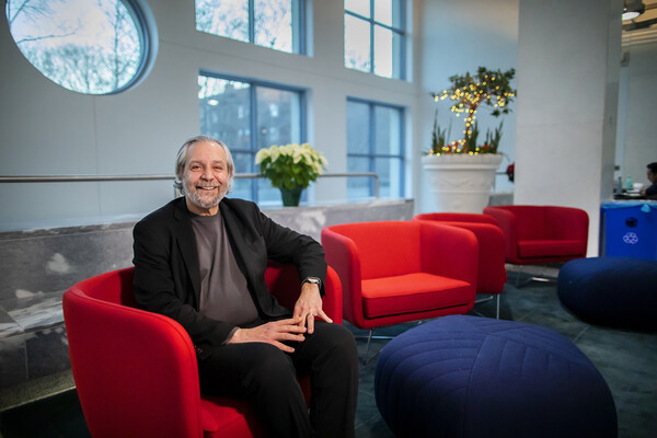 Delli Carpini sits on bright red chair in Annenberg School lobby