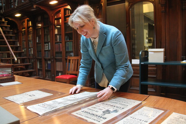 Librarian examines several playbills spread out on wood conference table in a historic library room lined with bookshelves filled with books.
