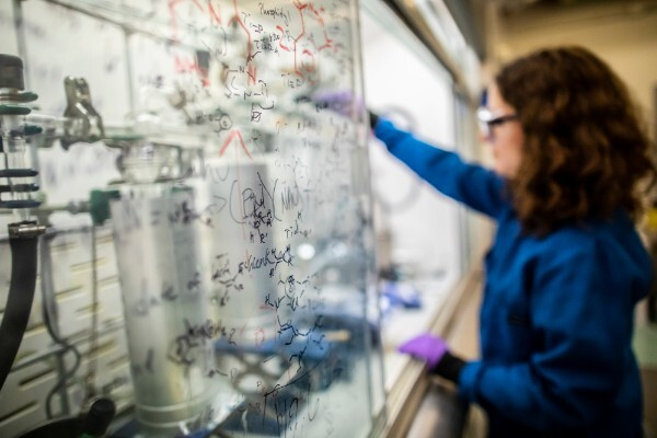 a close-up of chemical reactions written on a glass screen with a person in a lab coat working in the background