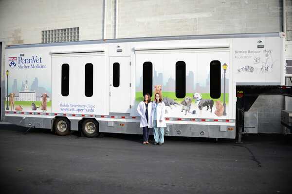 "Two women stand in front of a trailer with the words ""Penn Vet Shelter Medicine"" emblazoned on it and pictures of dogs and cats on the front"