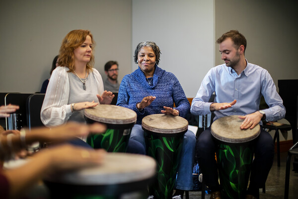 Two women and a man playing large bongo drums.