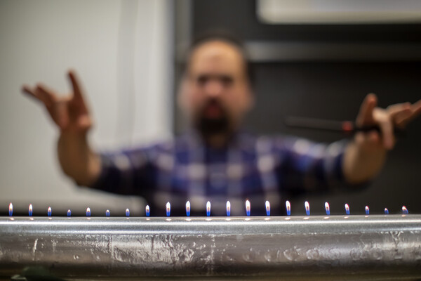 a metal tube with a line of flames coming out of the top and a blurred person posing in the background