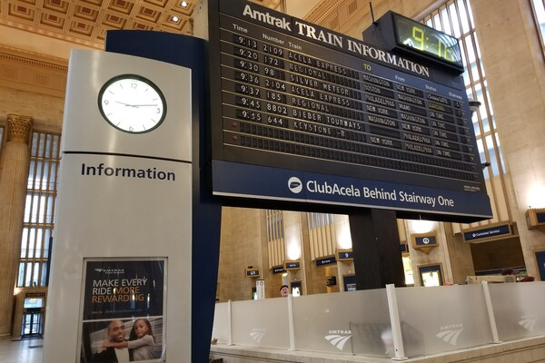 Split-flap board inside 30th Street Station surrounded by passengers and a clock
