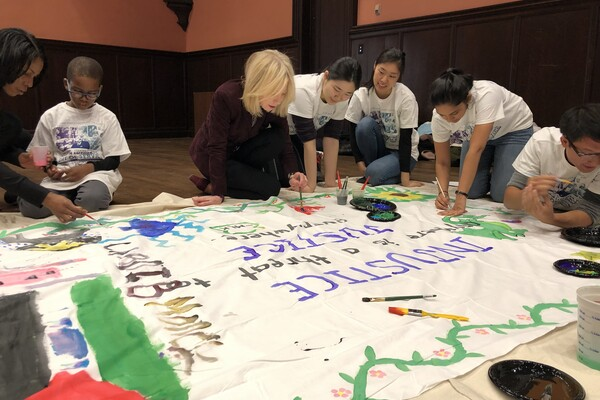 Amy Gutmann painting banners with children