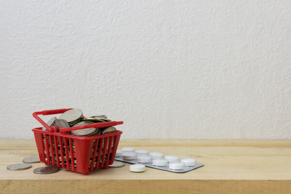 small shopping basket with coins and sleeve of pills on a shelf
