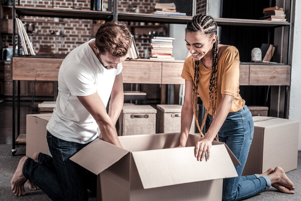 millenial couple packing a box