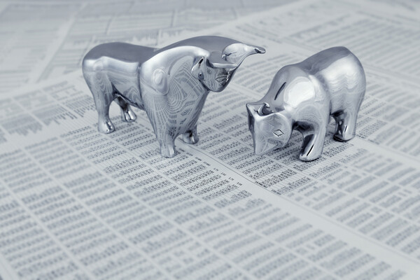 silver bull and bear figurines on top of a newspaper stock market section