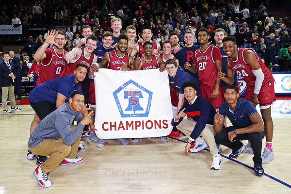Penn basketball players holder the Big 5 championship banner on the Palestra court