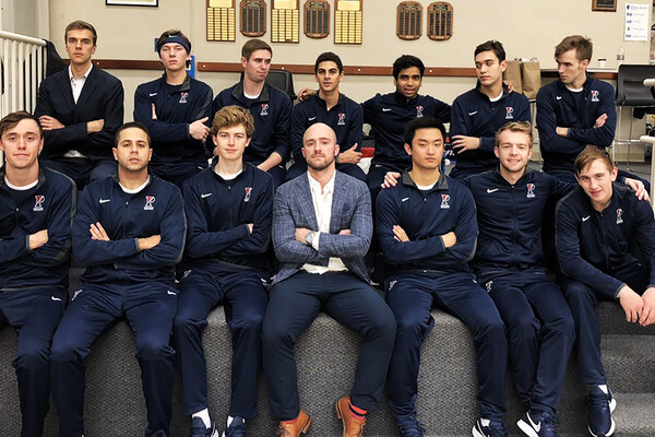 Men's squash players and the head coach pose on a bench