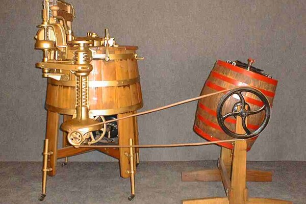 An old-fashioned washing machine, which looks like two wooden barrels on legs, next to each other and connected by large wiring.