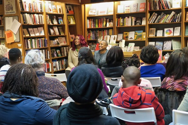 Feminista Jones and Tanji Gilliam seated in front of a small crowd at the Penn Book Center