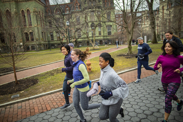 A group runs past trees and a green colored, Gothic-style building, Penn's College Hall.