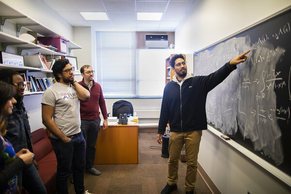 a group of students and a professor looking at a chalk board covered in math equations