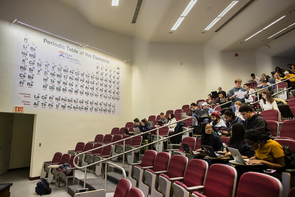 students in a classroom with a large periodic table behind their seats