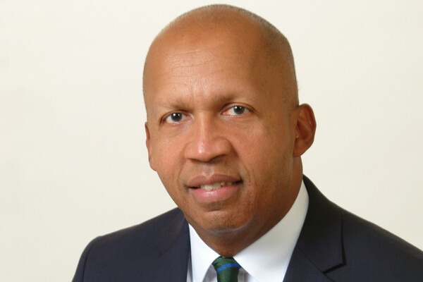 Bryan Stevenson wearing a black suit and green and blue striped tie.