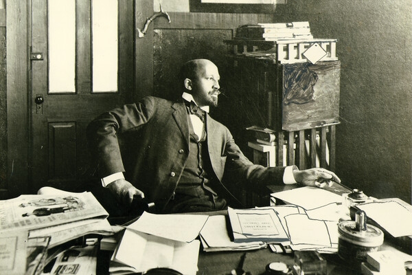 W.E.B. Du Bois sits at his desk in his office.