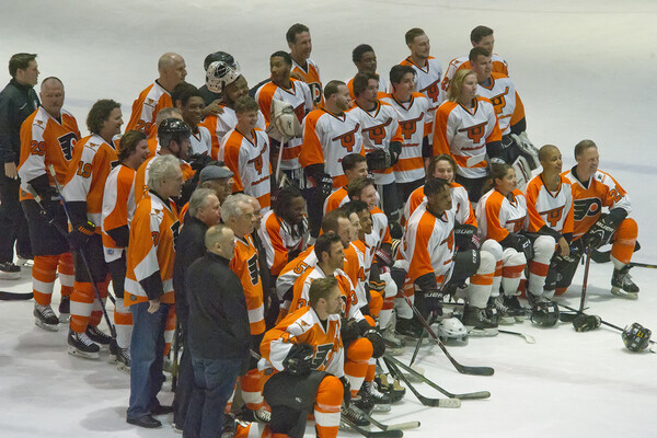 Members of Snider Hockey and Flyers Alumni pose on the ice for a group portrait