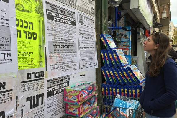 A girl in a blue fleece standing in front of a wall of black and white posters in Hebrew. Boxes of children's toys are in front of the wall.