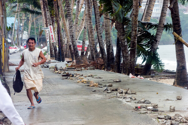 Man running during Super Typhoon storm in Philippines