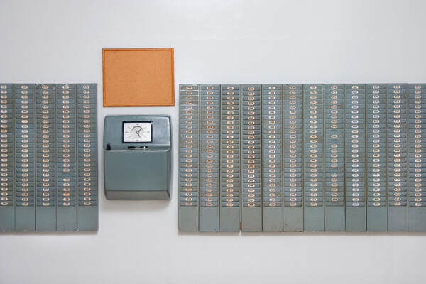 wall with time cards and a timeclock