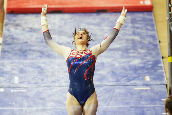 Sophomore gymnast Jordyn Mannino stands on the mat with her arms raised.