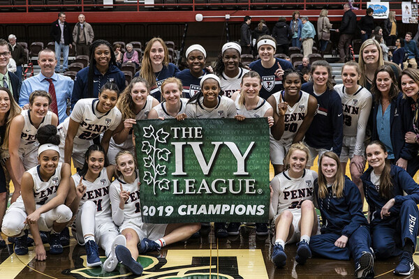 Members of the women's basketball team pose as a team with a banner that reads The Ivy League 2019 Champions on the court