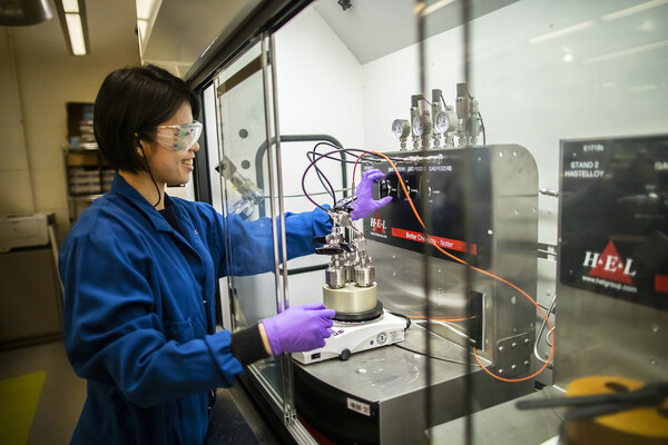 amy chu smiles while adjusting a knob on a metal piece of lab equipment