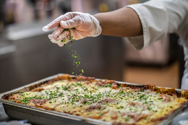 adding seasoning to lasagna at penn dining
