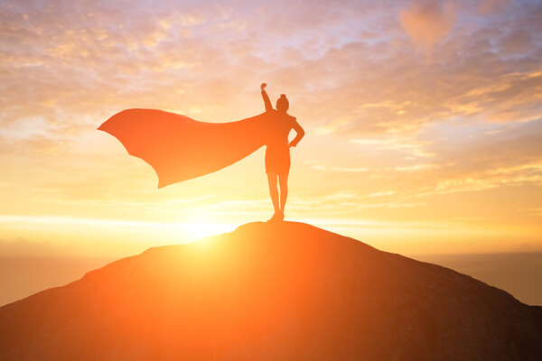 a silhouette of a woman with a cape standing on top of a hill