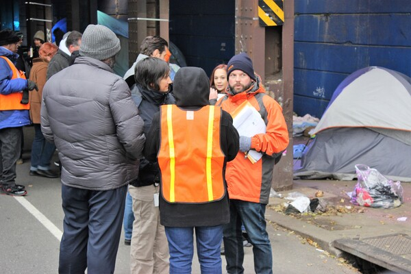 People standing in a group outside, with winter coats and orange vests, in front of a tent and plastic bags.