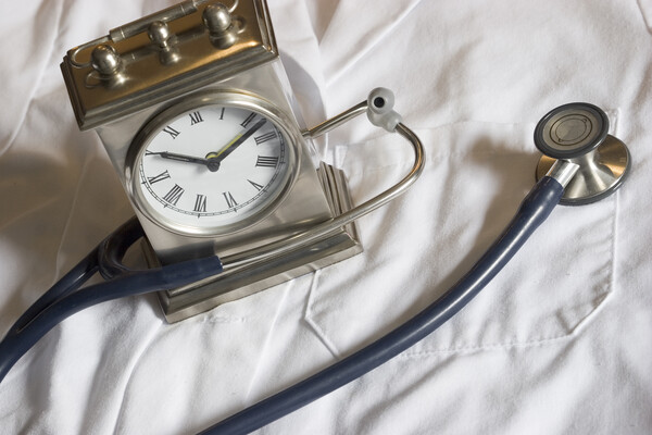A clock and a stethoscope on top of a white lab coat.