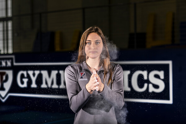 Jordyn Mannino of the gymnastics team claps chalk onto her hands in Hutchingson Gym.