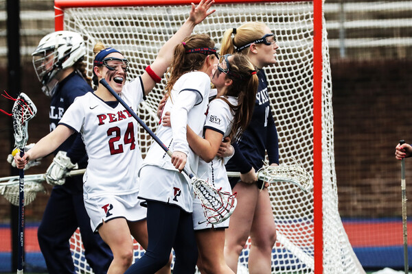 Penn women's lacrosse players celebrate after scoring a goal.
