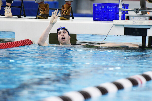 Mark Andrew holds up four fingers after winning four straight 200 IM at Ivy Championships.