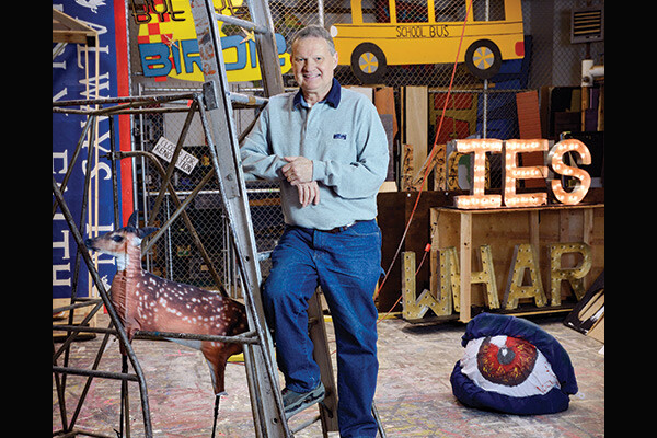 Peter Whinnery posing on a ladder in his workshop