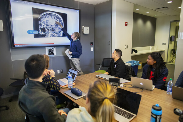 A man standing in front of a class of college students pointing to a scan of a brain.